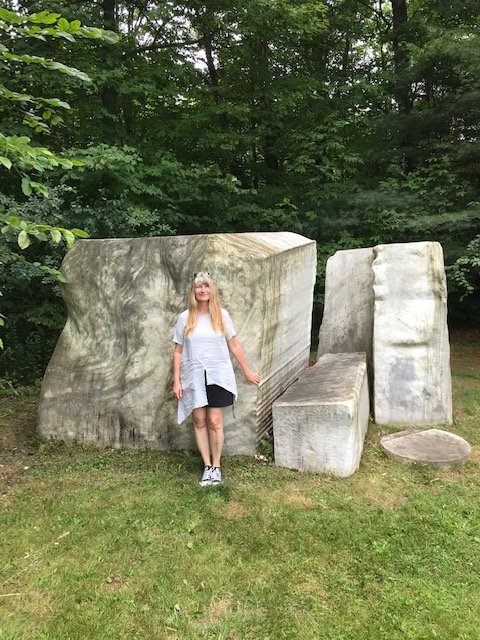 Sylvia Reischke, niece of Eric Reische standing next to one of his sculptures